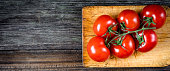 Fresh tomatoes on vine on wooden cutting board. Horizontal composition, copy space
