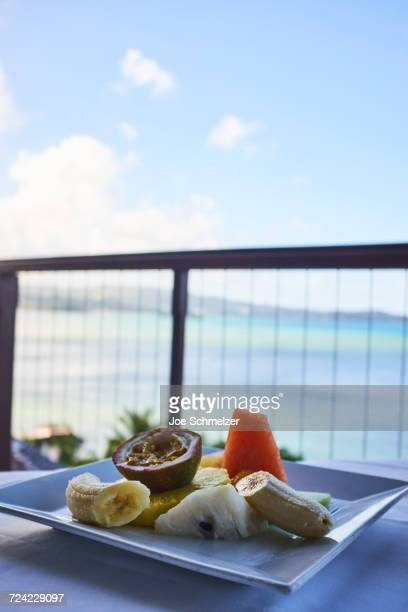 Fresh tropical breakfast fruit plate, with mango, papaya, banana and passion fruit, overlooking the water, Saint Lucia, Caribbean