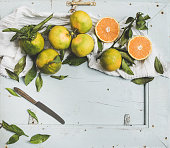 Fresh Turkish tangerines with leaves over blue rustic wooden backdrop, top view, copy space