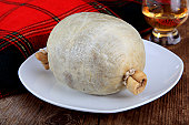 Uncooked Haggis Against A Tartan Background On A Rustic Wooden Table With A Tot Of Whiskey