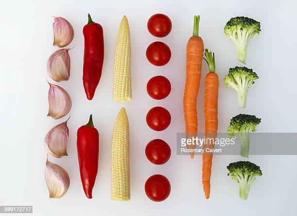 Fresh vegetables in parallel lines on white.