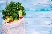 Market fresh vegetables hanging in a natural cotton recyclable shopping bag on wooden background