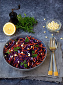 Fresh vegetables salad with purple cabbage, carrot, sprouted mung, parsley on grey clay plate on dark background. Cole Slaw Salad of red cabbage.