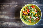 Fresh vegetarian salad on wooden background with blank space