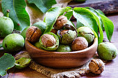 Fresh walnuts in a green shell with leaf, vintage wooden background, selective focus