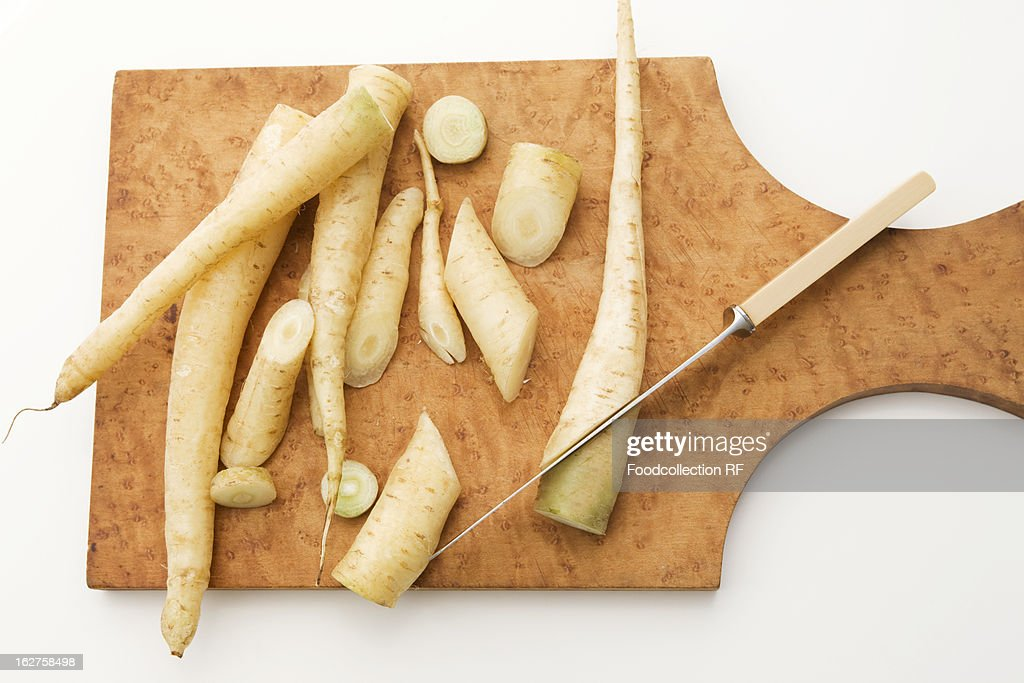 Fresh white carrots on cutting board with knife : Stock Photo