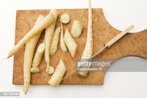 Fresh white carrots on cutting board with knife stock for White cutting board used for