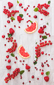Collection of fresh whole and sliced red fruits on white rustic background. Still life pattern background. Overhead view