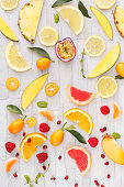 Collection of fresh whole and sliced yellow, orange and red fruits on white rustic background. Still life pattern background. Overhead view