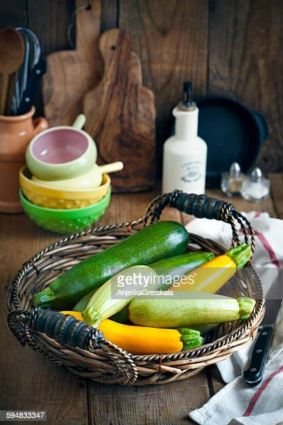 Fresh zucchini in basket on table