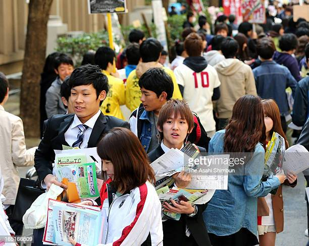 Freshers holding flyers inviting them to clubs walk in the campus after the entrance ceremony at Waseda University on April 1 2013 in Tokyo Japan