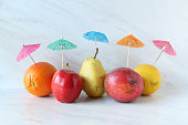 Five fresh fruits with drink umbrella. Copy space.