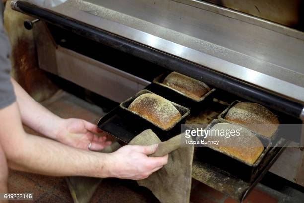 Freshly baked bread coming out of the oven at the Haxby Bakehouse York's artisan bakery in Haxby North Yorkshire United Kingdom on 17th February 2017...