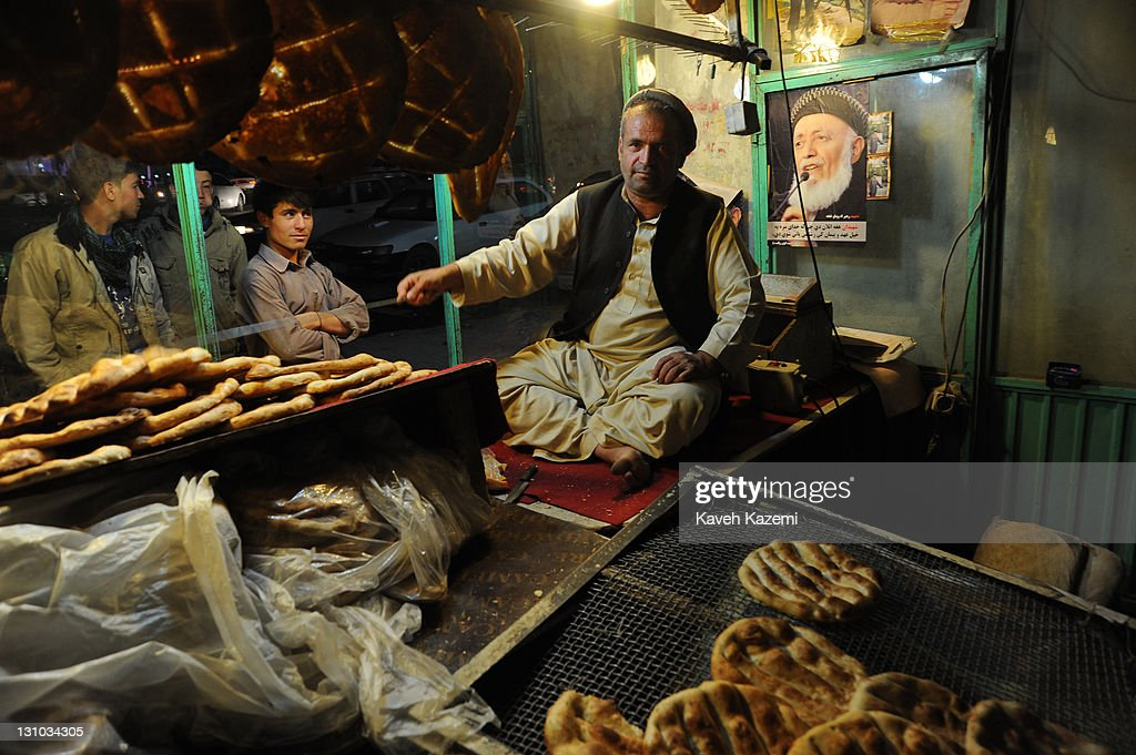 Freshly baked breads are displayed in the window where a picture of the recently assasinated ex Afghan president Borhaneddin Rabbani is posted on the wall in Shahr-e Now neighborhood on October 16, 2011 in Kabul, Afghanistan.