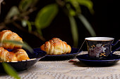 Freshly baked croissants and cup of tea on the table