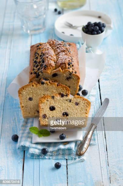 Freshly baked sliced blueberry cake loaf on blue wooden table top.