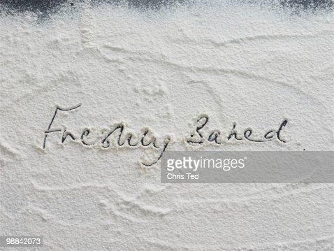Freshly baked written on flour : Stock Photo