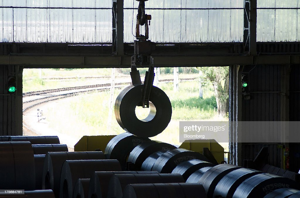 Freshly coiled rolls of steel are positioned by crane inside a storage facility at the ArcelorMittal Poland SA steel mill in Krakow, Poland, on Tuesday, Aug. 6, 2013. ArcelorMittal, the biggest steelmaker globally and in Poland, said on March 15 it expects European demand to slide before rebounding in 2014. Photographer: Will Boase/Bloomberg via Getty Images