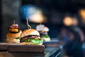 Close up image of a freshly flame grilled burger inside a bun, wilth lettuce, red onion, melted cheese and tomato. There are a few more burgers defocused in the background. The burger rests on a woode