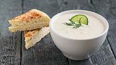 Freshly made tzatziki in a white bowl on a dark wooden table. Vegetarian Greek cuisine.