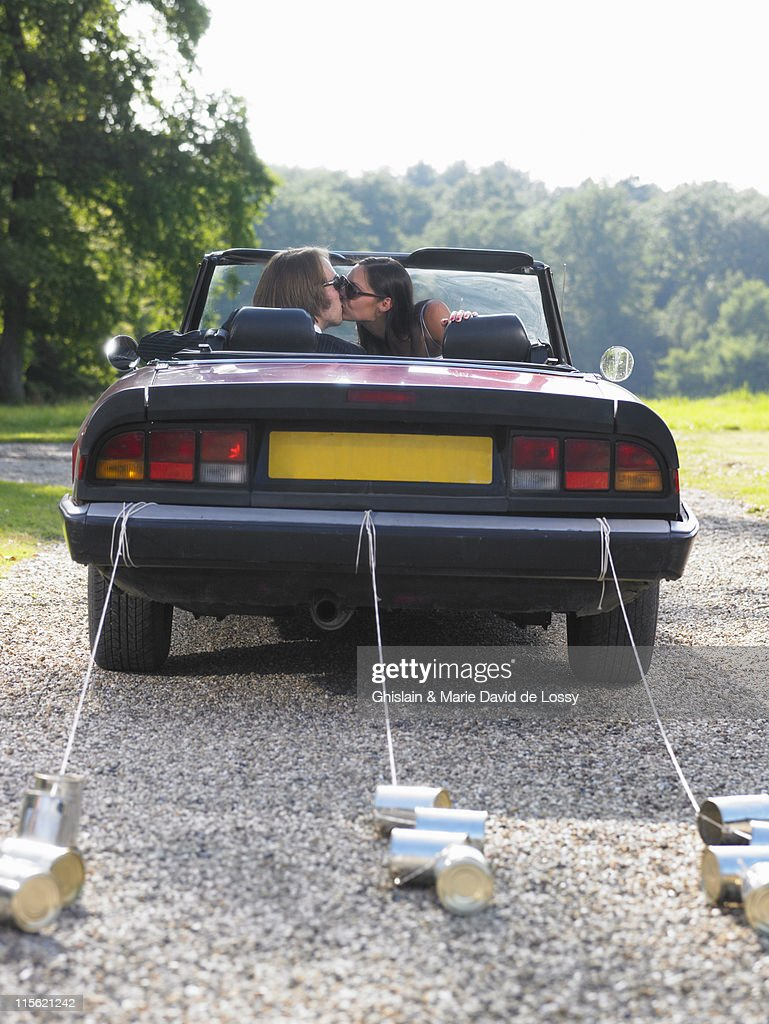 Freshly married couple kissing in car