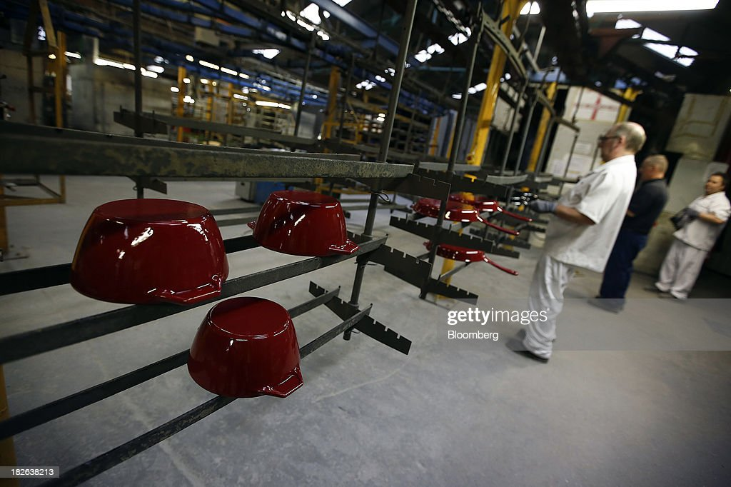 Freshly painted maroon cast iron AGA casserole dishes and frying pans, produced by AGA Rangemaster Plc, move along the production line during the manufacturing process at the company's plant in Telford, U.K., on Tuesday, Oct. 1, 2013. Euro-area factory output expanded for a third month in September as the 17-nation currency bloc's economic recovery gained momentum. Photographer: Simon Dawson/Bloomberg via Getty Images
