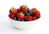 Freshly picked berries in white bowl.