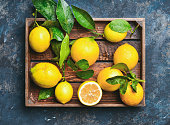 Freshly picked lemons with leaves in rustic wooden tray over dark blue shabby plywood background, top view