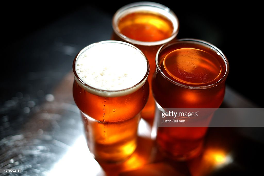 Freshly poured glasses of Russian River Brewing Company Pliny the Younger triple IPA beer sit on a counter at Russian River Brewing Company on...