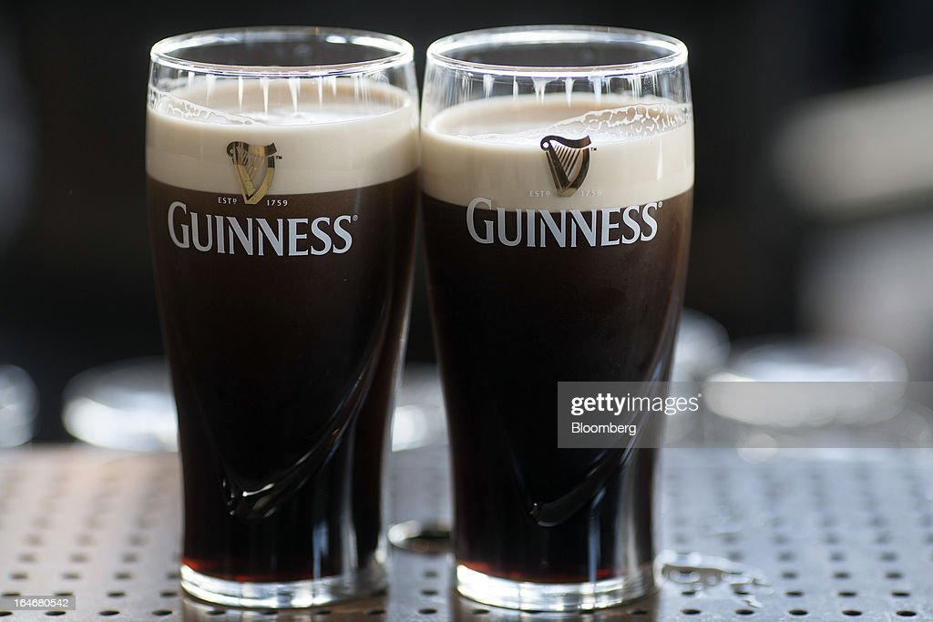 Freshly poured Guinness settles in two branded pint glasses on the bar in the Guinness Gravity Bar at the St. James's Gate Brewery, in Dublin, Ireland, on Saturday, March 16, 2013. Ireland's renewed competiveness makes it a beacon for the U.S. companies such as EBay, Google Inc. and Facebook Inc., which have expanded their operations in the country over the past two years. Photographer: Simon Dawson/Bloomberg via Getty Images