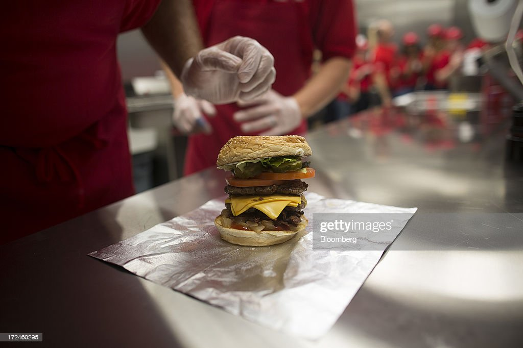 A freshly prepared cheeseburger sits on a kitchen counter at the first U.K. outlet of U.S. burger restaurant chain Five Guys in London, U.K., on Tuesday, July 2, 2013. Five Guys, which is set to open its first U.K. store in Covent Garden on July 4, is a family outfit that started in Washington, D.C., in 1986, and has expanded to more than 1,000 locations in the U.S. and Canada. Photographer: Simon Dawson/Bloomberg via Getty Images