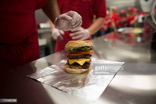 A freshly prepared cheeseburger sits on a kitchen counter at the first UK outlet of US burger restaurant chain Five Guys in London UK on Tuesday July...