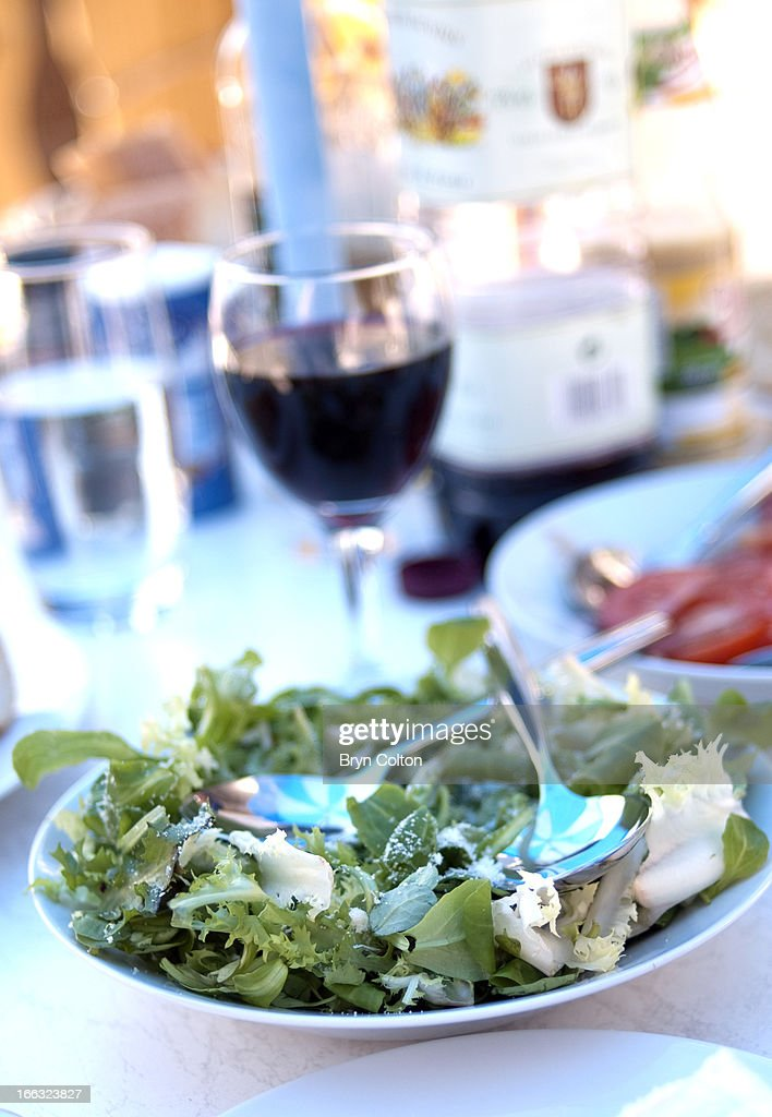 Freshly prepared green salad sprinkled with Parmesan cheese and a glass of Red wine sits ready for al fresco dining at a campsite in Saint-Jean-de-Monts, Vendee, France, on Sunday, August 20, 2006.