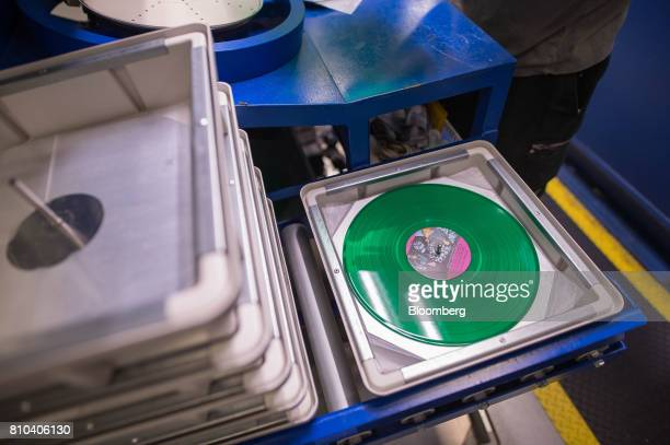 A freshly pressed vinyl record sits on the manufacturing line at the Precision Record Pressing facility in Burlington Ontario Canada on Friday June...