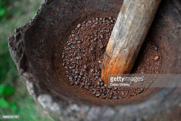Freshly roasted coffee beans being ground manually