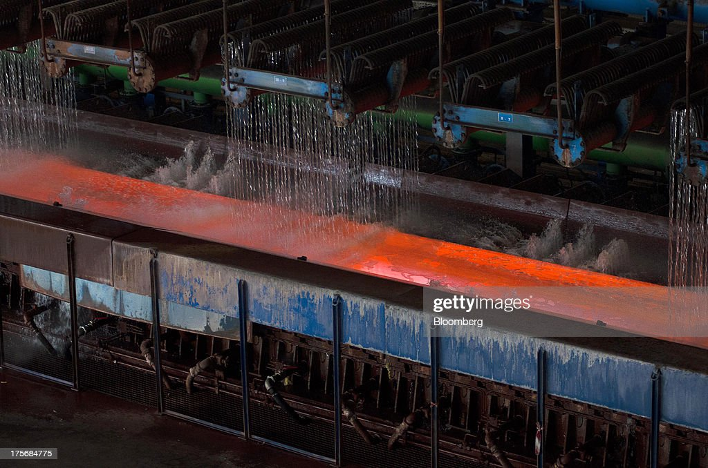 Freshly rolled steel is cooled by jets of water as it moves along the production line before being rolled into transport ready spools at the ArcelorMittal Poland SA steel mill in Krakow, Poland, on Tuesday, Aug. 6, 2013. ArcelorMittal, the biggest steelmaker globally and in Poland, said on March 15 it expects European demand to slide before rebounding in 2014. Photographer: Will Boase/Bloomberg via Getty Images