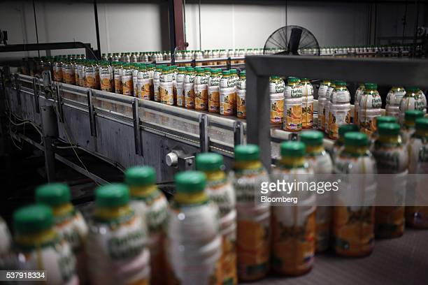 Freshlyfilled bottles of orange juice move down a production line at Florida's Natural Growers plant in Lake Wales Florida US on Thursday May 26 2016...