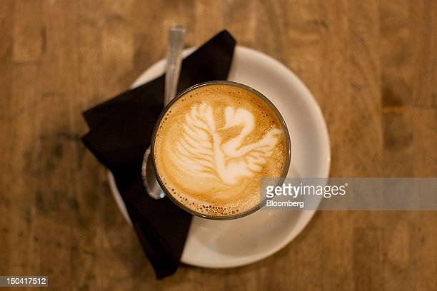 A freshlymade glass of 'cappuccino' coffee with a decorative swan design in the foamed milk stands on a counter inside a Taylor St Baristas coffee...