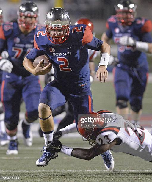 Fresno State quarterback Brian Burrell takes the ball down the middle of the field on a keeper as San Diego State's Damontae Kazee tries to make the...