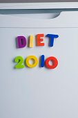 Colorful fridge magnet letters stuck on the door of a white fridge spelling out Diet 2010. Meant to remind people to start a diet in 2010. A New Year's Resolution. Think before you take something out