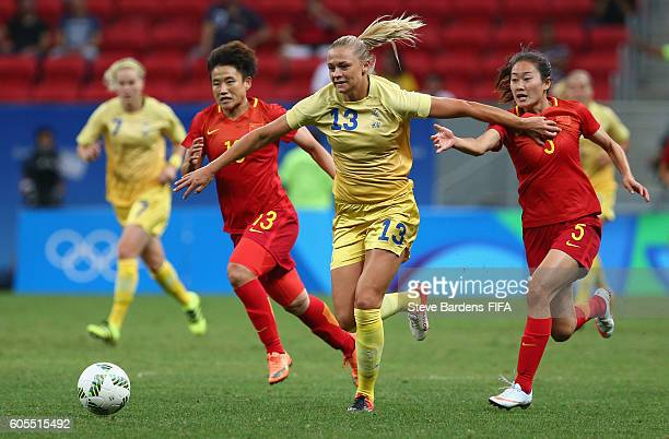 Fridolina Rolfo of Sweden breaks away from Fengyue Pang and Haiyan Wu of China during the Women's First Round Group E match between China PR and...