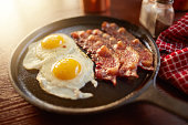 fried bacon and eggs in iron skillet shot with selective focus