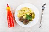 Fried beef meatballs and potatoes in plate, bottle with ketchup and fork on wooden table. Top view
