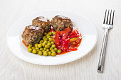 Fried beef meatballs with lecho and green peas in plate, fork on wooden table