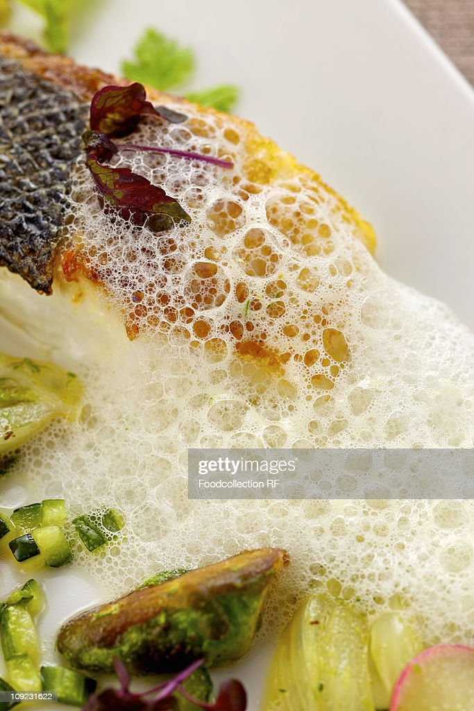 Fried branzino with spring vegetables and foam sauce in tray, close-up : Stock Photo