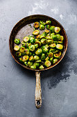 fried Brussels sprouts in frying pan on concrete background