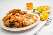 Plate of Fried Chicken and Mashed Potatoes with a small plate of yellow corn.