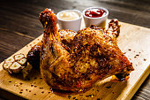 Roast chicken legs with French fries on wooden table