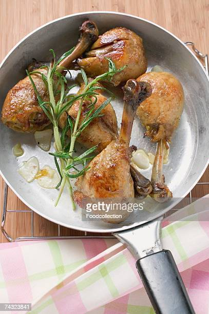 Fried chicken legs with rosemary in frying pan