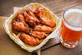 Fried chicken wings in a wicker plate and a large mug of beer